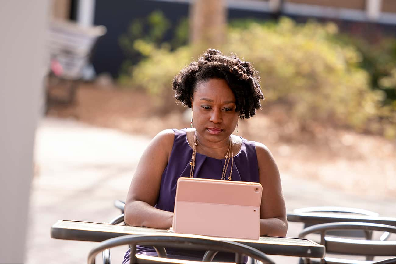 Black woman sitting at table with iPad